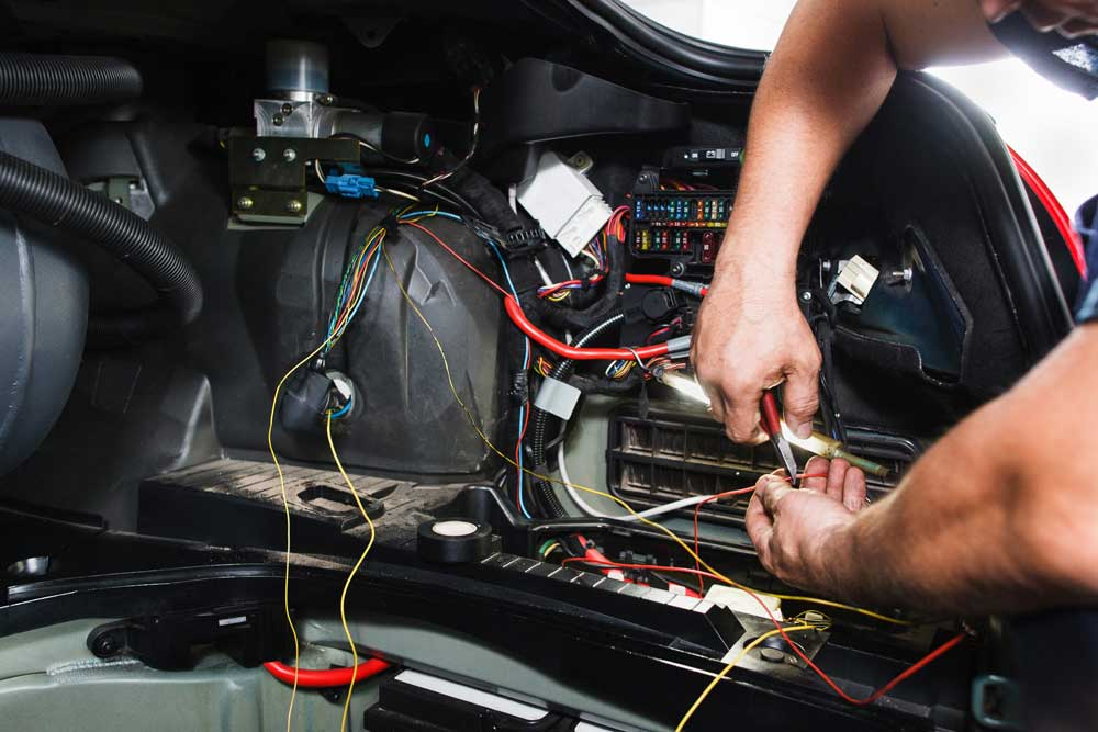 Car mechanic working on vehicle electronics